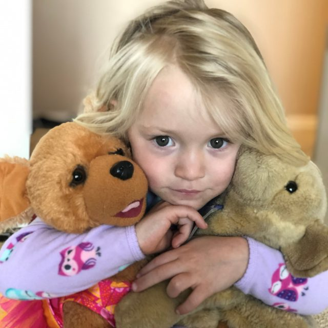 Little blonde girl holding teddy bears