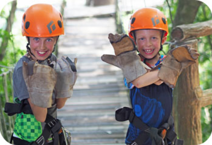 Two kids on a bridge with orange helmets