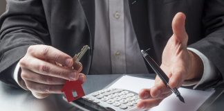 Should you manage your own rental property? Passive Income MD thinks not, especially if you're a physician! Pictured is a pair of hans, on holding a pen, another holding a set of keys, with a calculator and some paper on the table. The keys have a house keychain attached. This image is featured in a blog post on Passive Income, M.D. Enjoy!