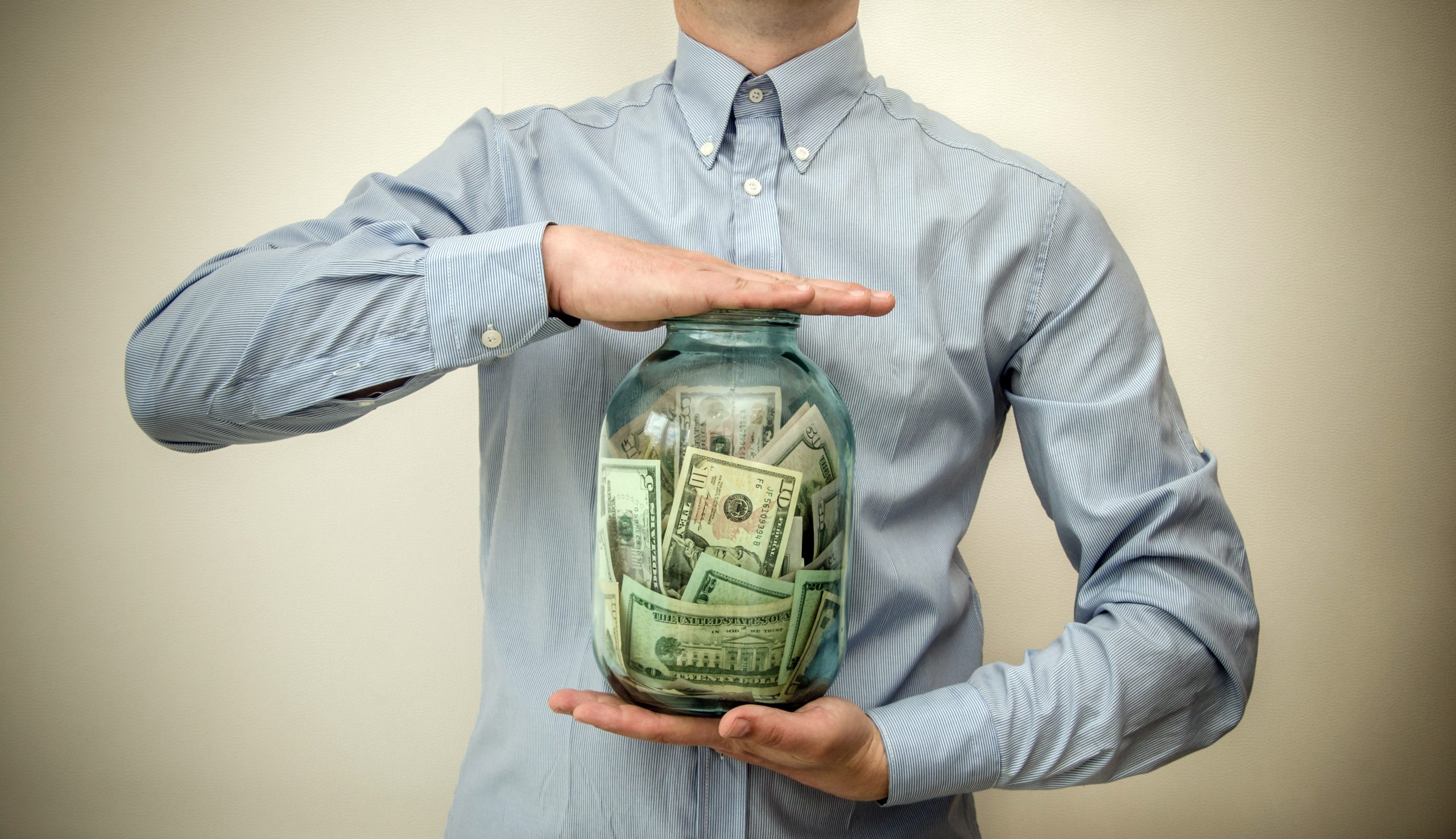 "A person holding a jar full of money. This image is featured in the blog post titled, ""Will more money make me happier?"" written by The Physician Philosopher and featured on the Passive Income, M.D. blog."