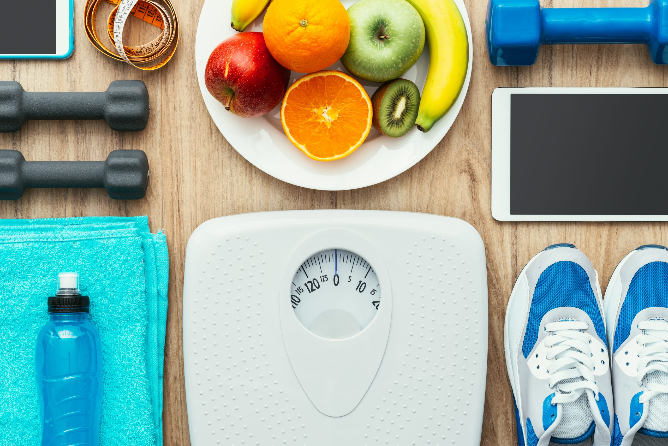 "Pictured is a blue water bottle, a bright blue towel, a white scale, a pair of blue and white tennis shoes, an electronic tablet, a set of black weights, a blue weight, a plate of fruits including an orance, a red apple, a greem apple, and a banana, a cell phone, and a measuring tape. This image is included in Passive Income MDs Saturday Syndication with White Coat Investor, titled ""5 Ways that Weight Loss is Like Investing."""