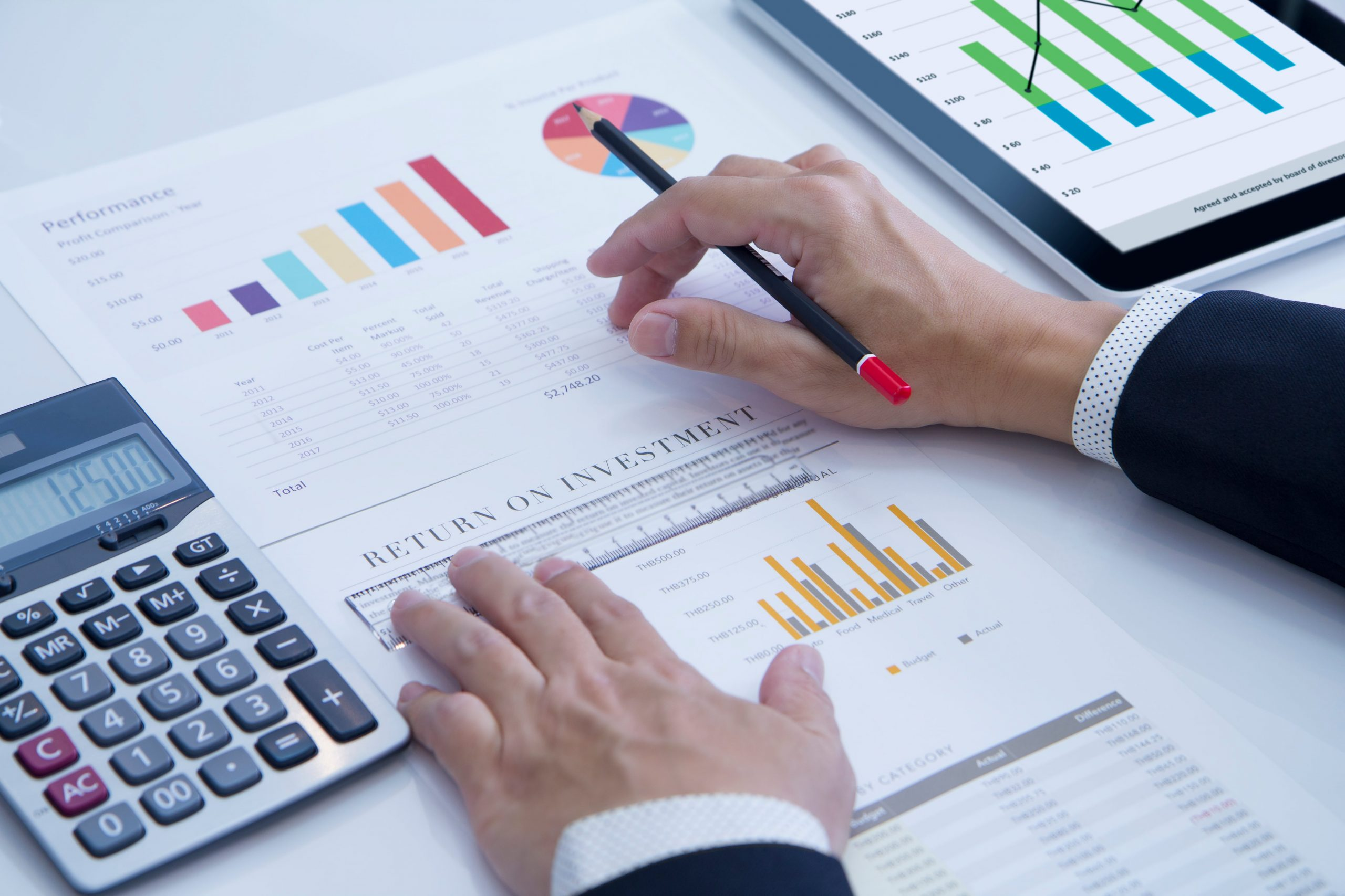 Two hands placed on a set of graphs dealing with yields and returns on investments. There is also a pen and calculator in the photo. This photo is featured on the Passive Income MD blog, where we have shared content from the White Coat Investor about yields and returns.