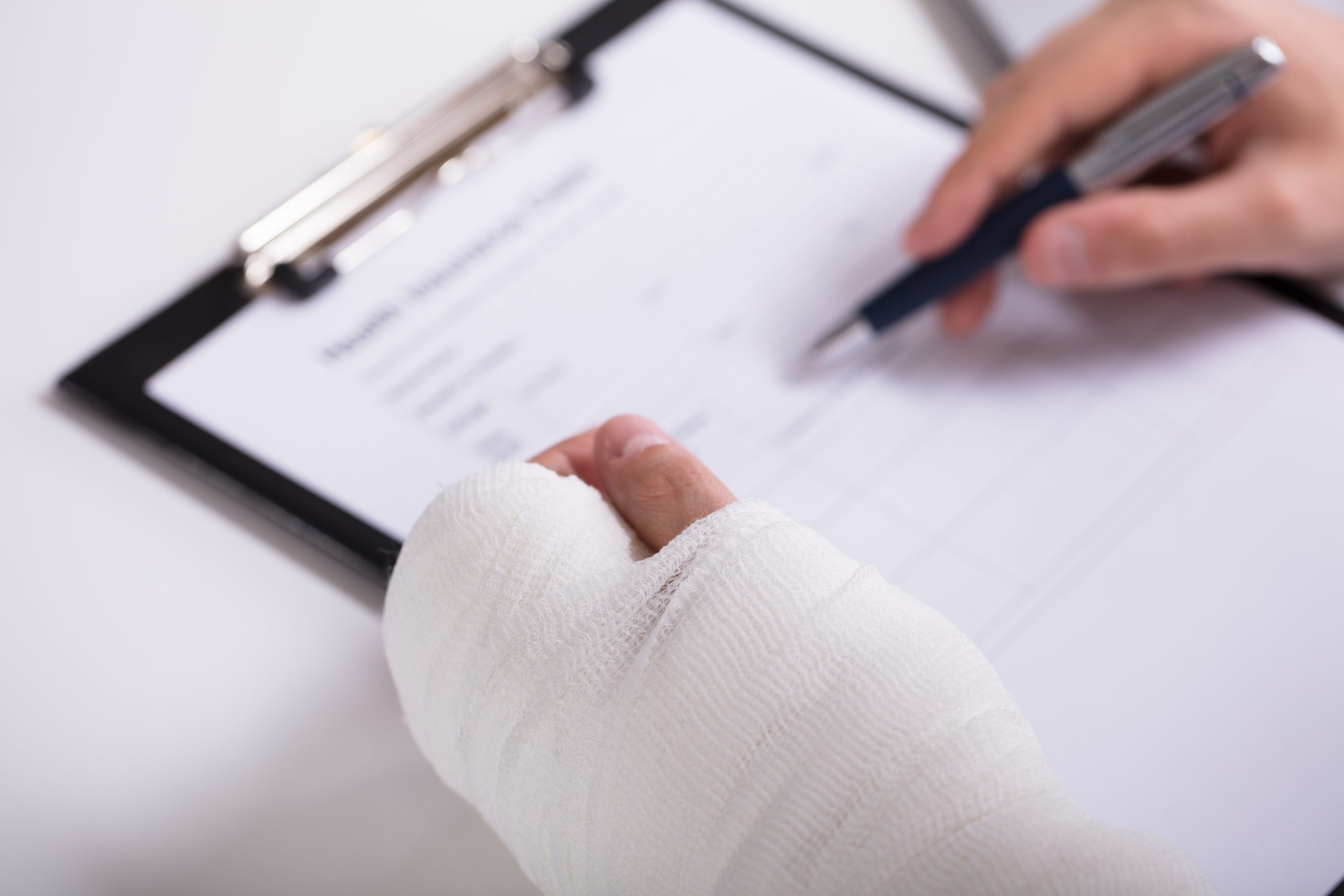 A broken left hand in a cast and a right hand filling out a form. This image is featured on the Passive Income MD blog in a partnership post with Pattern. Get your disability insurance through Pattern, especially if you're a physician. You can get started here: https://www.patternlife.com/quote/physician-disability-insurance-quote-request?uclickid=ebmti5e4b33a3821e8674872457&campid=481226&utm_source=&utm_medium=&utm_campaign=&utm_term=&utm_content=