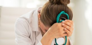 "Pictured is a female physician who is head down in her hands while holding a teal green stethoscope. She apprears to be distressed and miserable. This photo is featured on the Passive Income MD blog, where we have featured The Physician Philosopher in a blog post titled, ""I Am a Doctor and I Hate My Job."""